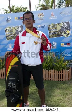 PUTRAJAYA, MALAYSIA - OCTOBER 9: Febiandi Andri Muhamad from Indonesia wins the bronze medal at 2011 IWWF Asian Waterski & Wakeboard Championships in Putrajaya, Malaysia on October 9, 2011. - stock photo