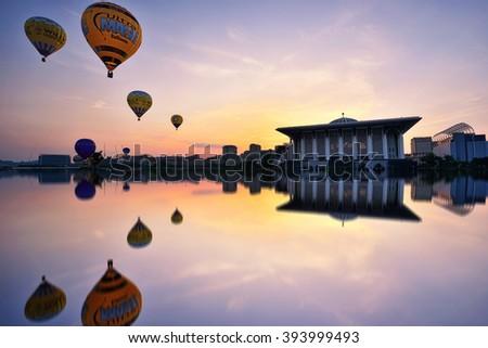 PUTRAJAYA - MARCH 13, 2016 - Hot air balloons in various designs flying over Sultan Mizan Zainal Abidin Mosque at the 8th Putrajaya International Hot Air Balloon Fiesta in Putrajaya, Malaysia. - stock photo