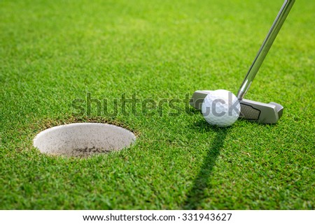 Putting a golf ball on the green - stock photo