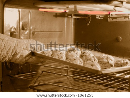 putting cookies in oven for baking - stock photo