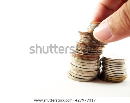 Putting down coins on pile of collected money, isolated on white background 
