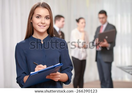 Putting down meeting minutes. Young cheerful businesswoman putting down something at her clipboard while her team standing on the background - stock photo