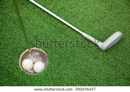 Putting golf club on green grass with golf ball in the hole - top view - stock photo