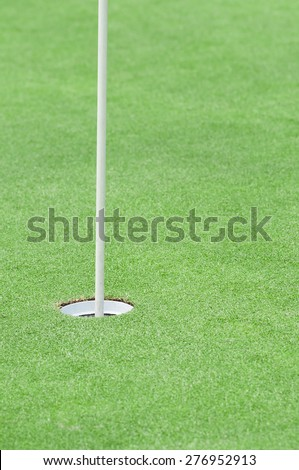 Putting green with flag pole - stock photo