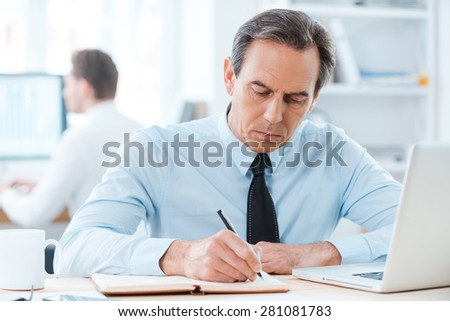 Putting his ideas on paper. Serious businessman in formalwear writing in note pad while sitting at his working place  - stock photo