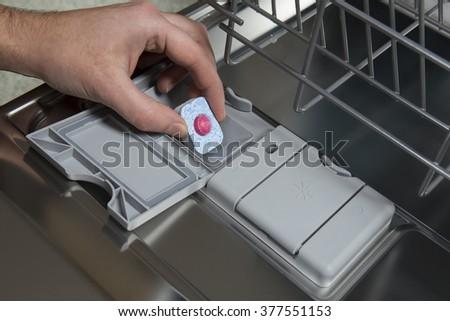 Putting tablet in dishwasher machine - stock photo