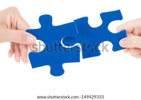 Putting the next pieces together for solving the jigsaw - stock photo