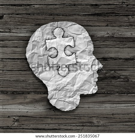 Puzzle head solution concept as a human face profile made from crumpled white paper with a jigsaw piece cut out inside the brain area on an old wood background as a mental health symbol. - stock photo