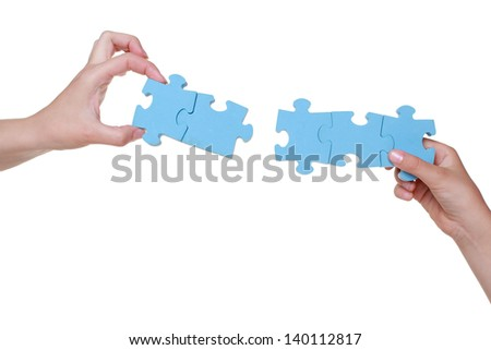 Puzzle in hands of mother and daughter - stock photo
