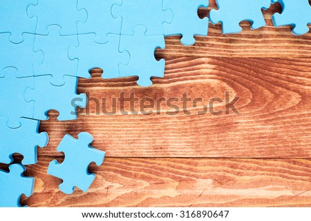 Puzzle on brown wooden background.Team business concept - stock photo