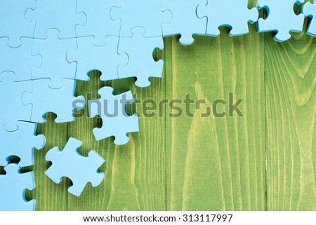 Puzzle on green wooden background.Team business concept - stock photo