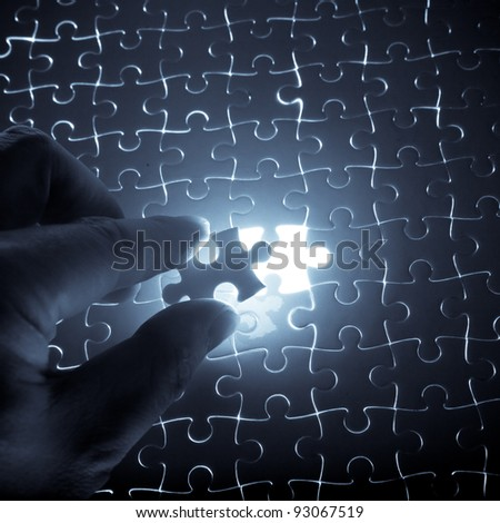 puzzle piece down into place - stock photo