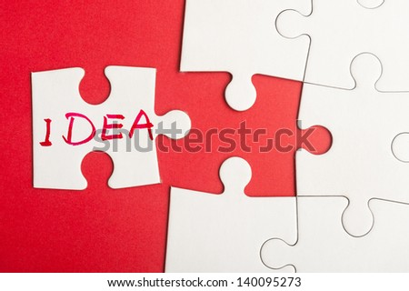 Puzzle piece which written idea word inserted into group of white paper jigsaw puzzles - stock photo