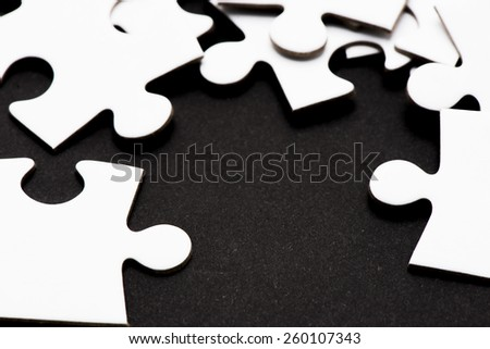 Puzzle pieces on black background. Conceptual image of connection, solution and business strategy. - stock photo