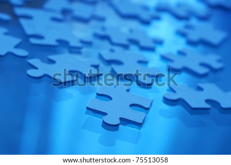 puzzle pieces on glass,  fluorescent mode selected for white balance - stock photo