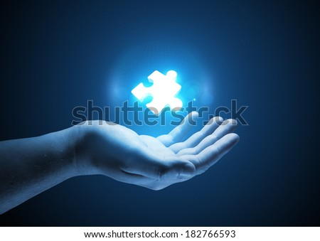 Puzzle Solutions. Conceptual illustration. A man holding a glowing single puzzle piece. - stock photo