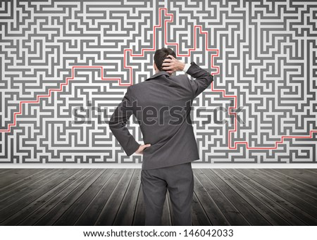 Puzzled businessman looking at a maze drew on a wall - stock photo