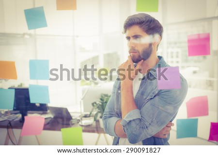 Puzzled businessman looking post its on the wall in the office - stock photo