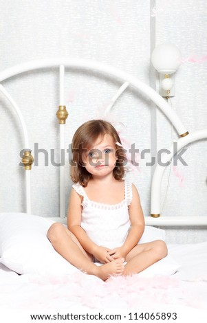 Puzzled little girl sit in bed - stock photo