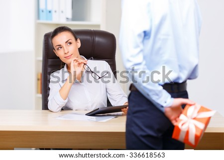 Puzzled look. Young attractive office manager looks curious while looking at her male colleague who is hiding present behind his back. - stock photo