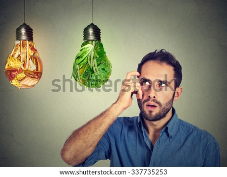 Puzzled man thinking looking up at junk food and green vegetables shaped as light bulbs making decision isolated on gray background. Diet choice right nutrition healthy lifestyle wellness concept - stock photo