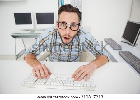 Puzzled nerdy businessman working on computer in his office - stock photo