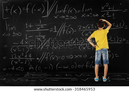 puzzled student looking at a huge blackboard with a difficult equation, school concept - stock photo