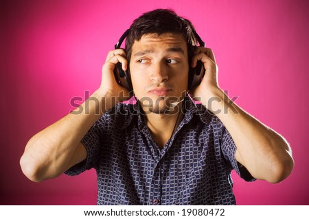 Puzzled young guy listening music with headphones, pink background. - stock photo
