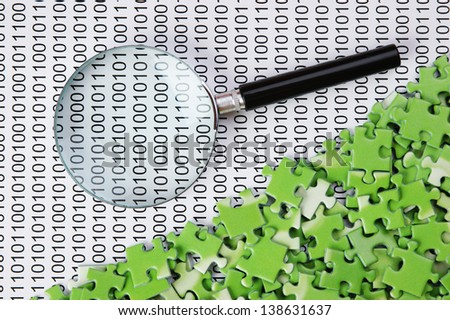 puzzles and magnifying glass on a binary code - stock photo
