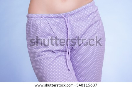 Pyjamas pajamas. Closeup of female legs wearing violet pyjama pants on blue. Pajama party at night. Studio shot. - stock photo