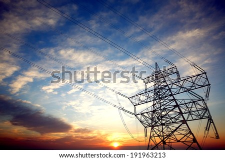 Pylon and power lines at sunset with nice sky and sun - stock photo