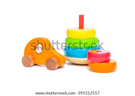 Pyramid build from colored wooden rings and a wooden orange toy car. Toys for babies and toddlers to joyfully learn mechanical skills and colors. Studio shot on white background. - stock photo