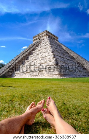 Pyramid Castillo in Chichen itza and legs of couple relaxing on grass, Mexico - stock photo