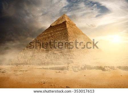 Pyramid in sand dust under gray clouds - stock photo