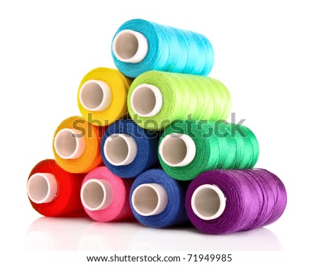 Pyramid of many-coloured bobbins of thread isolated on white - stock photo