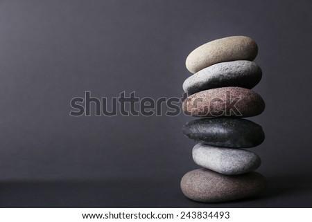 Pyramid of spa stones on dark background - stock photo