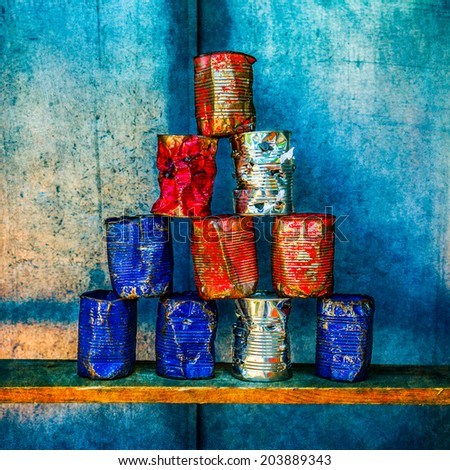 Pyramid of ten empty soup cans of white, blue and red colors against grunge metal wall. Some cans are shot through. Soup Cans - Square Meal. Andy Warhol inspired. - stock photo