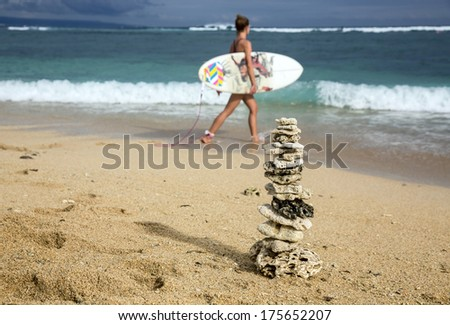 Pyramid of the corals on the ocean shore. Beautiful young surfer girl with board goes into the ocean - stock photo