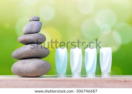 Pyramid of the stones and bottle with green bokeh on wooden. - stock photo