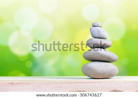 Pyramid of the stones isolated on green bokeh background - stock photo