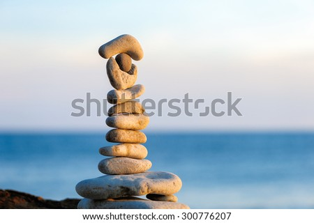 Pyramidal group of stones on the coast - stock photo