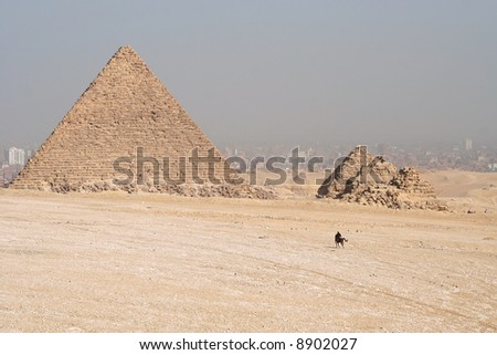 Pyramids in Egypt. Cairo in the background in smog and manr riding a horse. - stock photo