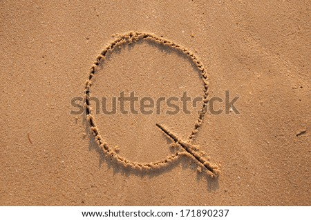Q text written in the sandy on the beach - stock photo
