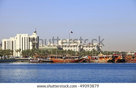 Qatar's foreign ministry (left) and Emiri Diwan ruler's administrative palace (centre with flag) seen across Doha Bay, with fishing dhows moored in front of the government buildings. - stock photo
