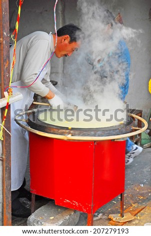QIBAO, SHANGHAI-DECEMBER 4, 2007: vendor cooking a flat bread. Qibao water village is Shanghai tourist attraction with 1000000 visitors year. - stock photo