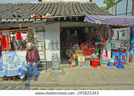 QIBAO, SHANGHAI-MARCH 16, 2010: lady sitting near  a typical Chinese drug store. Qibao water village is Shanghai tourist attraction with 1000000 visitors year. - stock photo