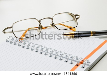 qlasses, notebook and the pen - stock photo