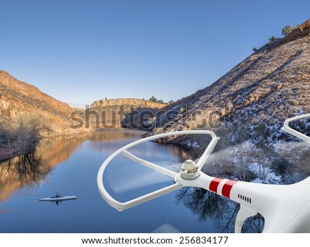 quadcopter drone flying over lake with a canoe - Horsetooth Reservoir near Fort Collins, Colorado - stock photo
