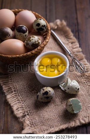 Quail and chicken eggs on wooden background. Selective focus.  - stock photo