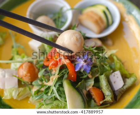quail egg on chopsticks with japanese green vegetables salad on background - stock photo
